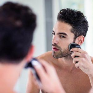 Man shaving in the mirror in the bathroom