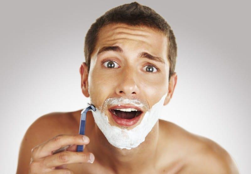 Man shaving in bathroom with manual razor
